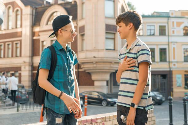 La amistad y la comunicación de dos adolescentes es 13, 14 años de edad, fondo calle ciudad - foto de stock