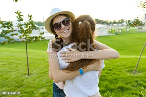 istock The friendship of two teenage girls, best girlfriends have fun in nature, on the green lawn of recreation park and entertainment. Embrace the greeting and parting. 1014364198
