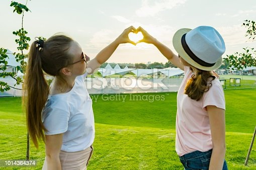 istock The friendship of two teenage girls, best girlfriends have fun in nature, on the green lawn of recreation park and entertainment, show hands on heart on sunset background in park. 1014364374