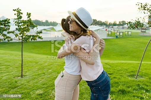 istock The friendship of two teenage girls, best girlfriends have fun in nature, on the green lawn of recreation park and entertainment. Embrace the greeting and parting. 1014364376