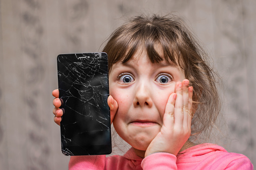 Portrait of a scared little girl with a broken mobile phone. A sad child broke the screen of a mobile phone. Cracked display in hand kids.