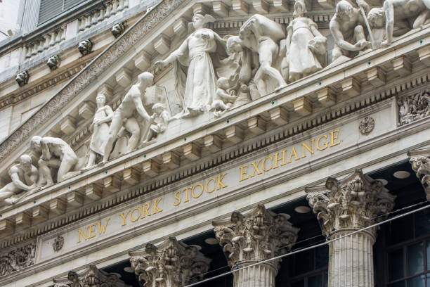 the front entrance and sign of the new york stock exchange at wall street - new york stock exchange stock pictures, royalty-free photos & images