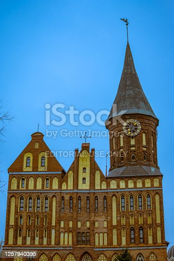 The front facade of the Cathedral with a clock on a tower and a weather vane against the background of a turquoise sky on the Kant island, Kaliningrad, Russia, 05.11.2018. High quality photo