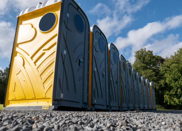The front of a row of grey and yellow portable chemical toilets The front of a row of grey and yellow portable chemical toilets, being used at an outdoor event. They are located on a gravel area, ready for use. Note the pattern on the sides of each toilet door and on the sides. portable toilet stock pictures, royalty-free photos & images