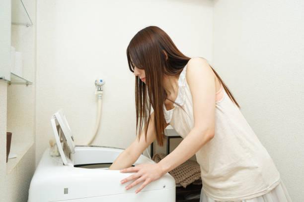 洗濯機の前にいる女性 ストックフォト