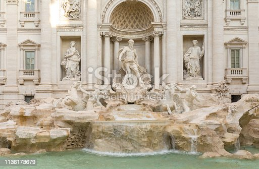 The front view of the Trevi Fountain, Rome, is captured on an idyllic day. There are a lot of marble sculptures of men, women, and horses near the majestic building in the fountain, and the water in the fountain is turquoise.