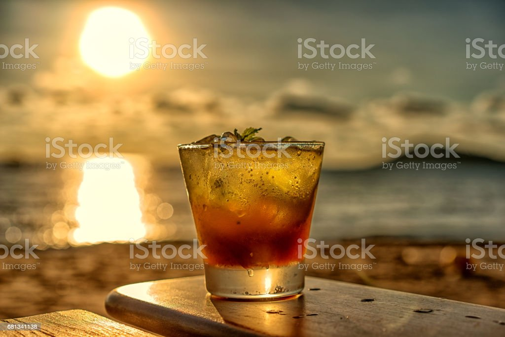 The frozen glass of Mojito cocktail on the beach at sunset with blurred background. stock photo