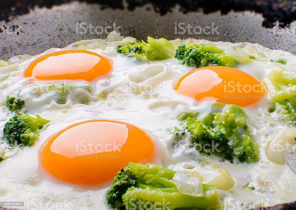 The frying pan fried eggs with broccoli and wood background stock photo