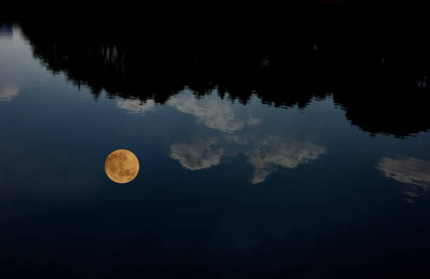 The full moon reflected on the lake surface stock photo