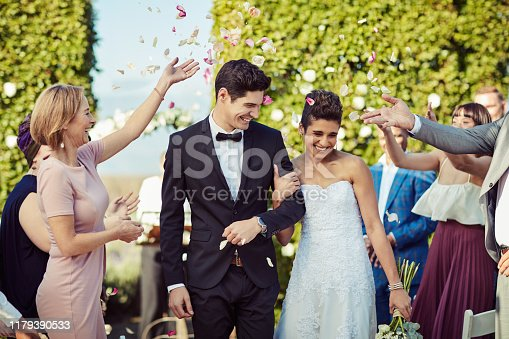 Shot of a happy young couple getting showered with flower petals after getting married in a garden