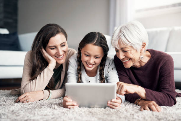 the fun never ends with a tablet around - granddaughter and grandmother stock photos and pictures