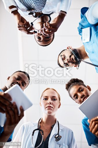 Low angle shot of a group of young doctors using smart devices in a hospital