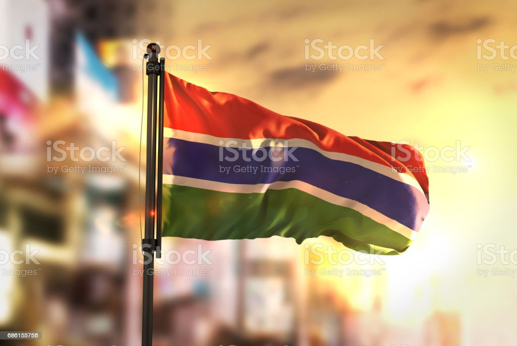 The Gambia Flag Against City Blurred Background At Sunrise Backlight stock photo