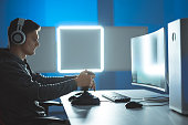 istock The gamer with headphones playing video games on the illuminated background 1277112418