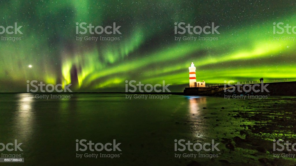 The Gardur lighthouse under the light of the aurora borealis stock photo