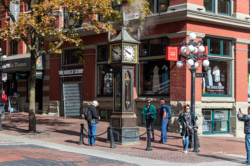 Crowd gathers around the world famous Gastown Steam Clock on Water St. in downtown Vancouver, BC.
