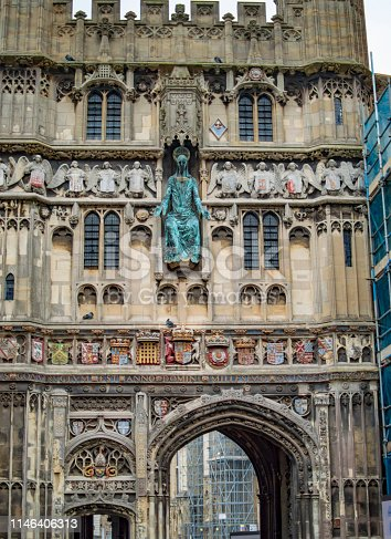 The gate of Canterbury cathedral and the arched entry point with great art work on the walls.