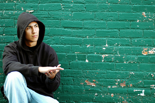 Color photo of a young, hispanic man in an alley crouching by a green brick wall thinking about his life on the street as a gang member.