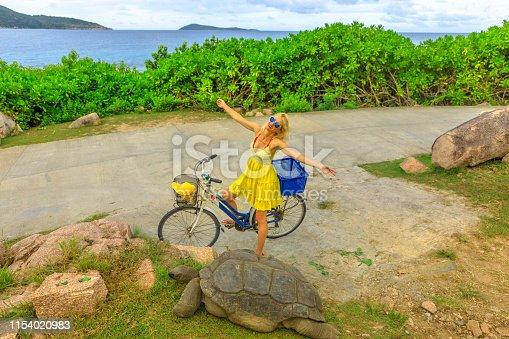 Happy caucasian lifestyle tourist woman on bicycle near Anse Banane in La Digue, Seychelles, with Aldabra Giant Tortoise, Aldabrachelys gigantea. Popular tourist attraction. Natural sea background.