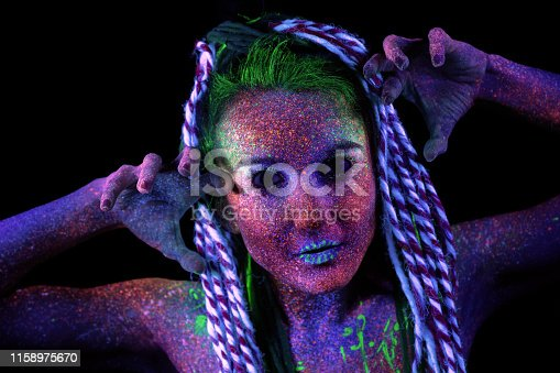 The girl aliens looks to the camera. shrugs her shoulders, ultraviolet make-up. She holds her hands near her face, next to her ears.