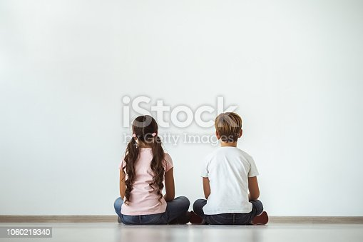 585604690istockphoto The girl and a boy sitting on the floor on the white wall background 1060219340
