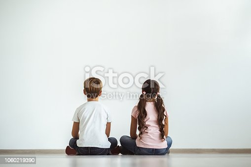 585604690istockphoto The girl and a boy sitting on the floor on the white wall background 1060219390