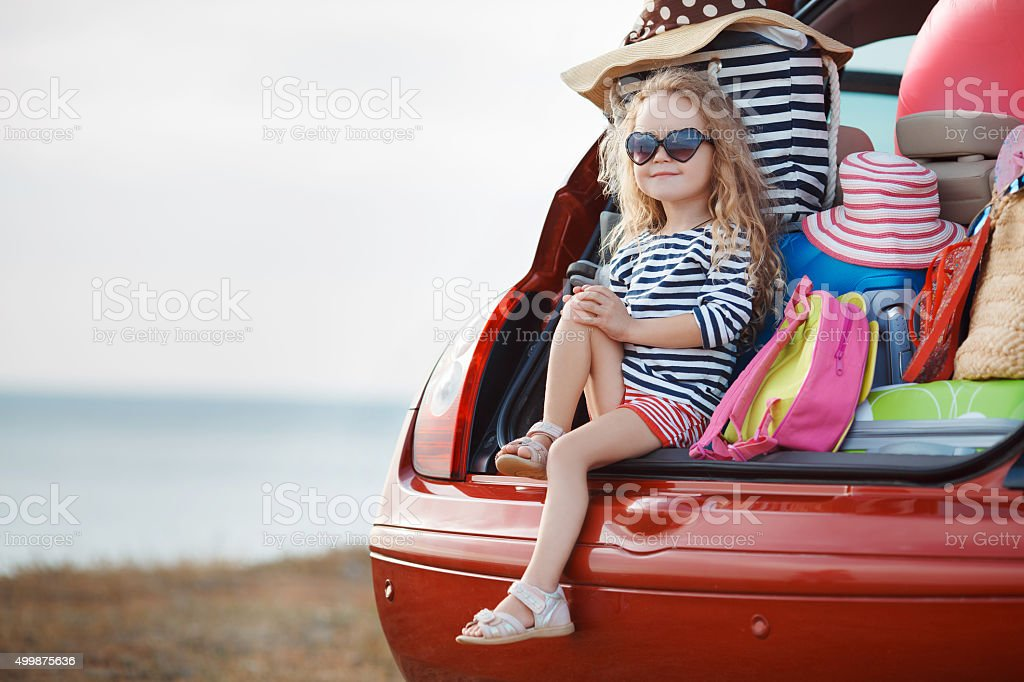 The girl and stuff in the open trunk stock photo