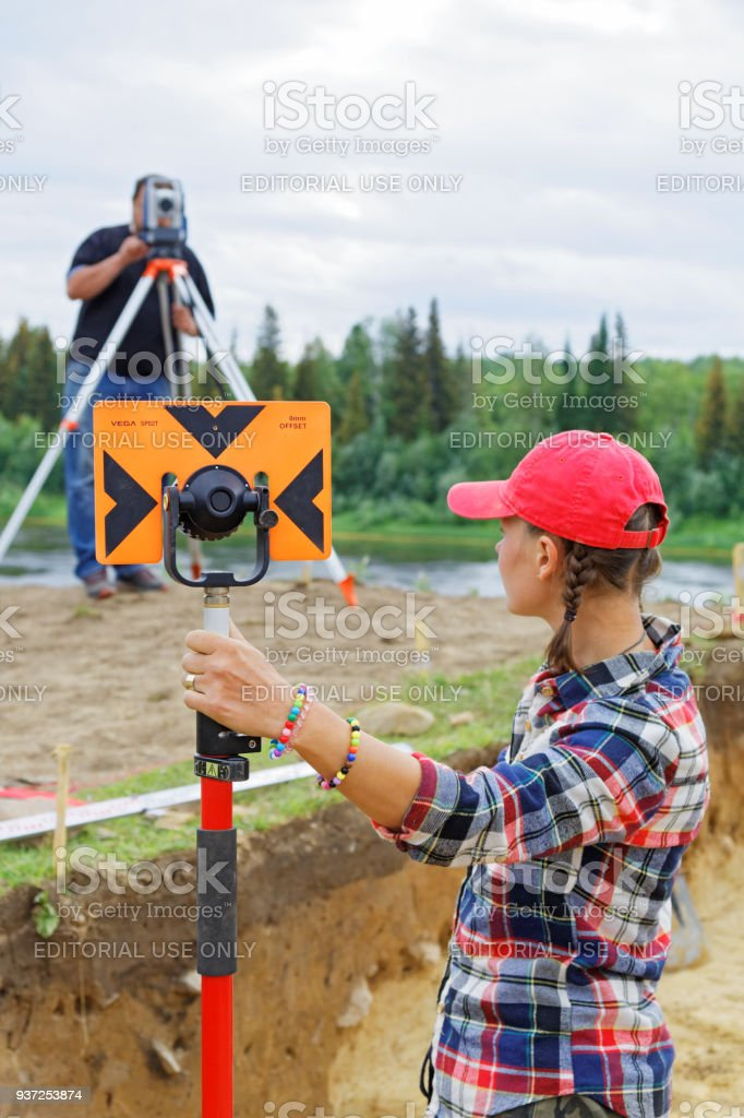 The girl and the man make a geodetic survey of the area.The coordinates of archaeological finds are determined stock photo