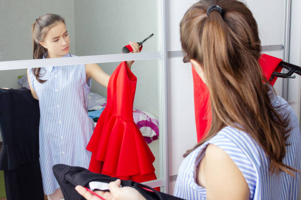 The girl at home in front of the mirror tries on dresses, chooses an outfit stock photo