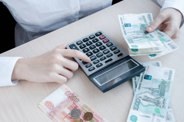 테이블에서 여자는 계산기와 이익 고려 - 러시아 루블 뉴스 사진 이미지