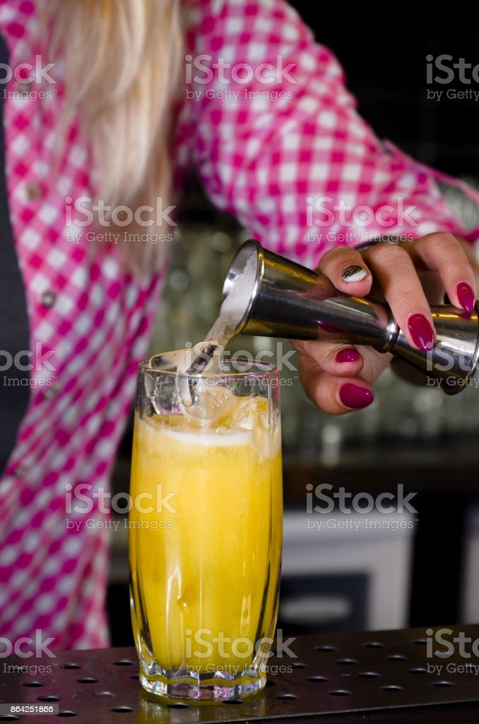 The girl bartender makes a cocktail pours it into a glass standing on the bar. Female hands prepares a drink in the nightclub royalty-free stock photo