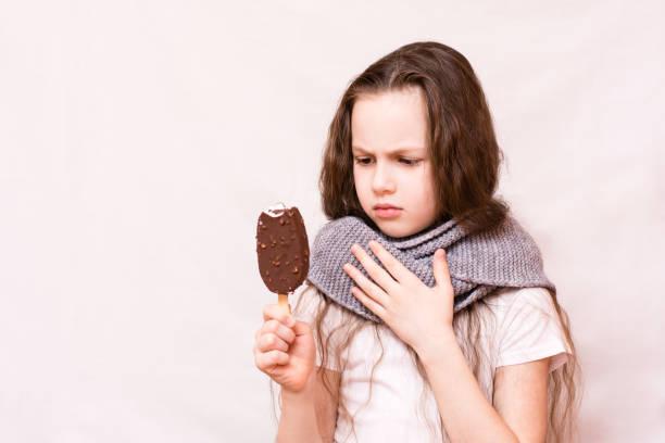 Kız dondurmayı ısırdı ve boğazını aştı. stok fotoğrafı