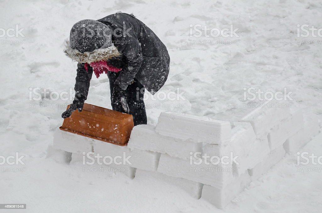 The girl building a snow home stock photo