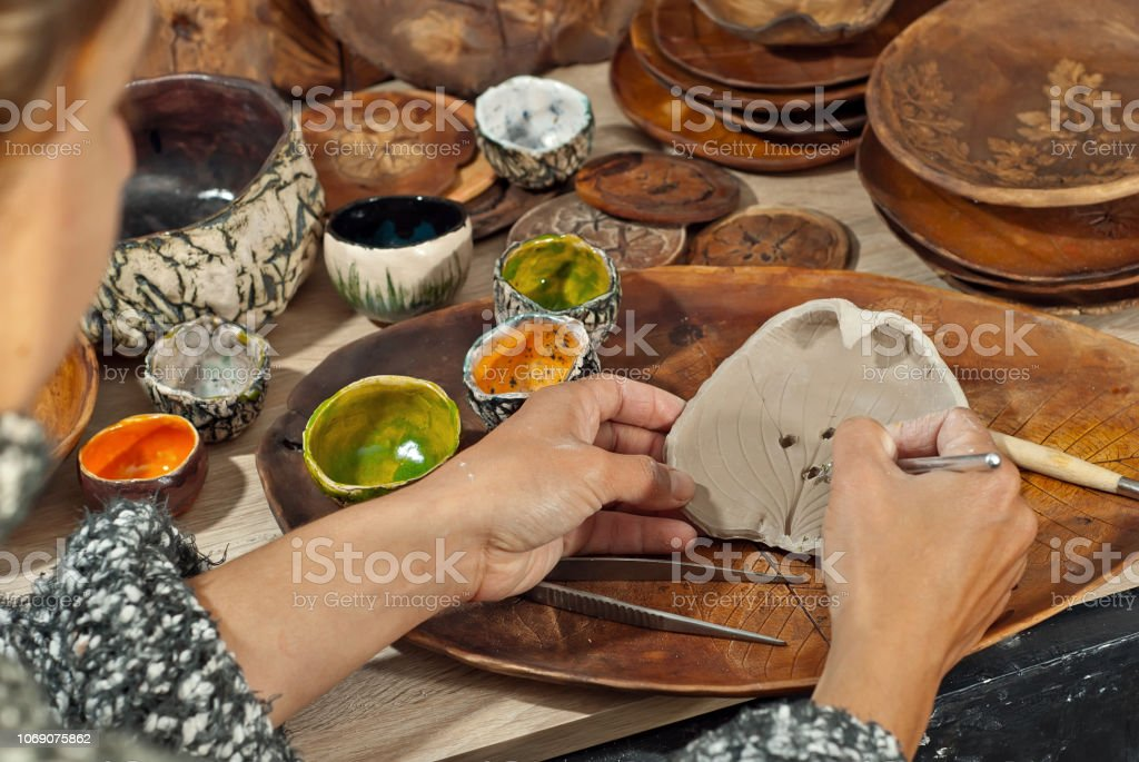 The girl carves an ornament on an earthenware bowl. Handmade products...