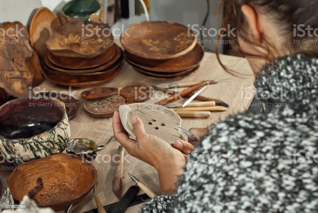 The girl carves clay dishes with tools. Handmade products on the...