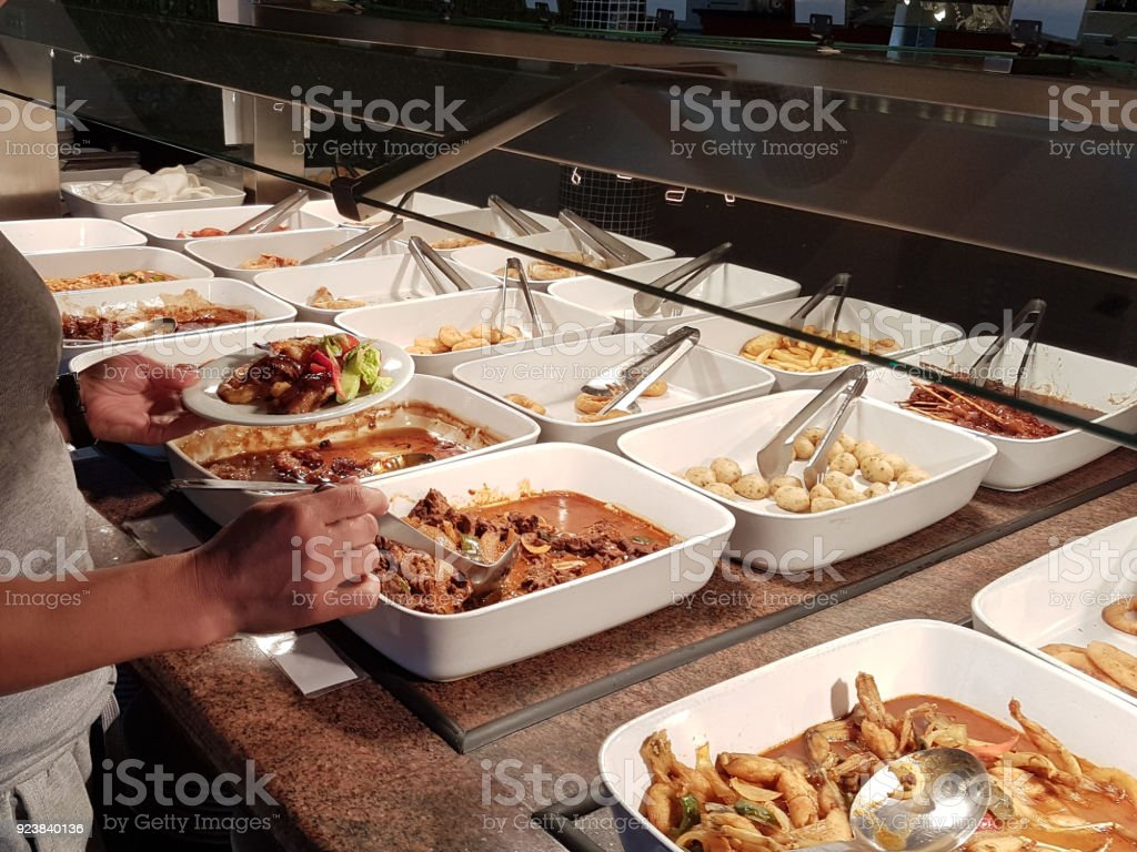 The girl chooses food in an Asian restaurant Pay-what-you-want  chooses among the numerous egozotic dishes. Indochinese Kitchen. The room is darkened with light meals. stock photo