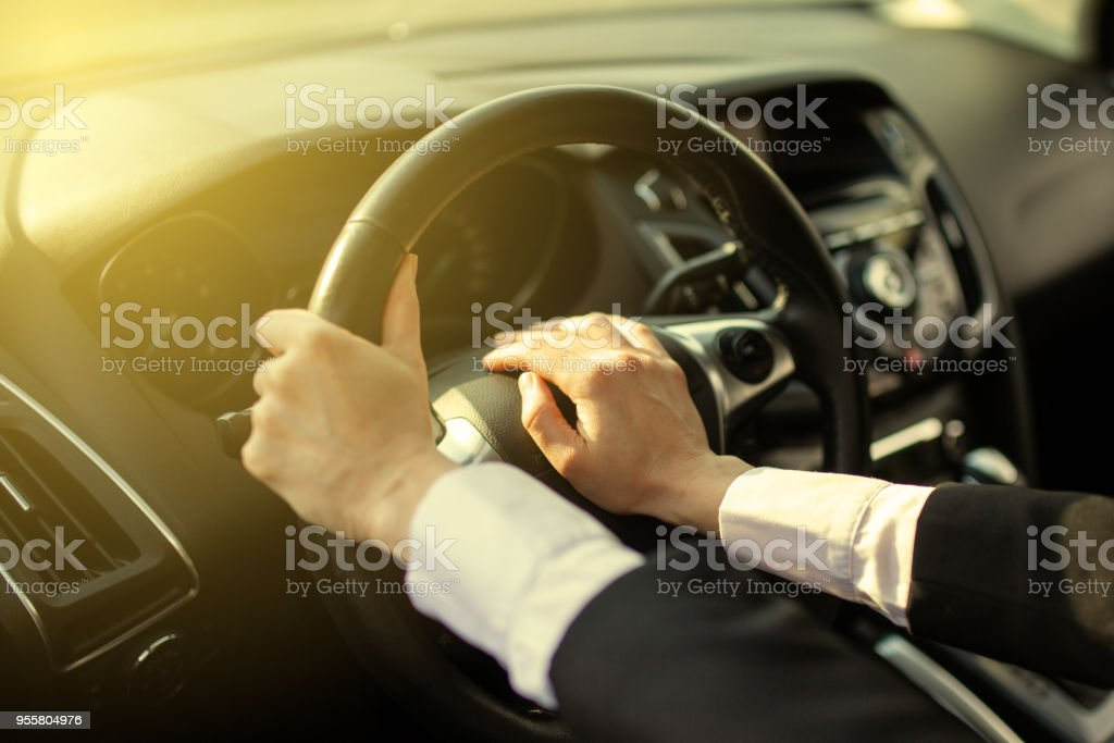 The girl clicks a hand on the signal on the steering wheel of the car