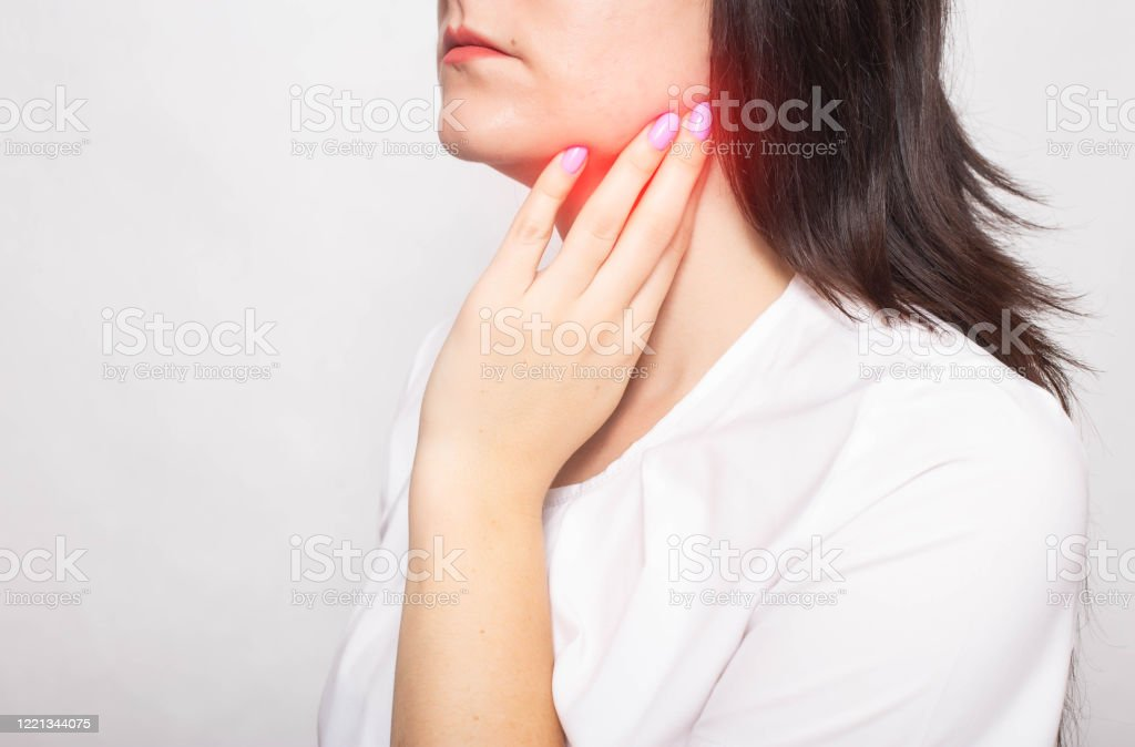The girl clings to the inflamed salivary gland in which pain. Concept of salivary gland disease, mumps, cancer, copy space The girl clings to the inflamed salivary gland in which pain. Concept of salivary gland disease, mumps, cancer, copy space, retention cyst Backgrounds Stock Photo