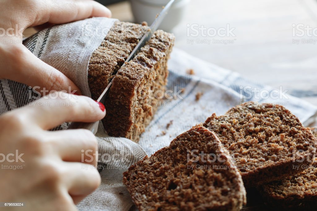 The girl cuts whole-wheat rye bread on a wooden table. stock photo