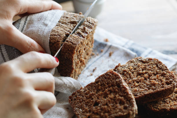 The girl cuts whole-wheat rye bread on a wooden table. - foto stock