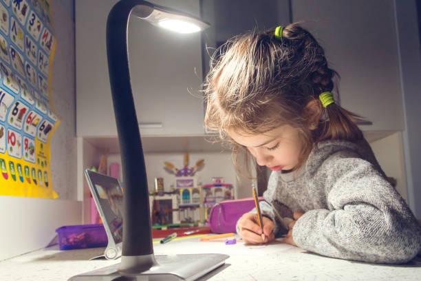 das mädchen zieht am tisch im lichte der lampe - kinderzimmer tischleuchten stock-fotos und bilder