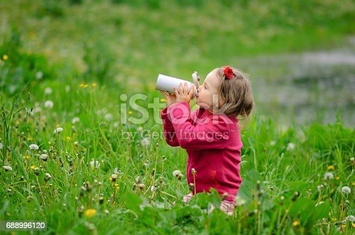 istock The girl drinks water from a thermos bottle. Mug-thermos, spring grass, curly hair, outdoor recreation, healthy lifestyle, environmental protection, protection of nature, conscious consumption 688996120
