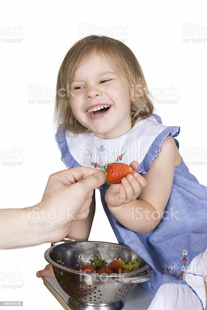 The girl eats a strawberry stock photo