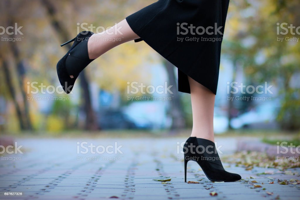 The girl goes in high-heeled boots stock photo