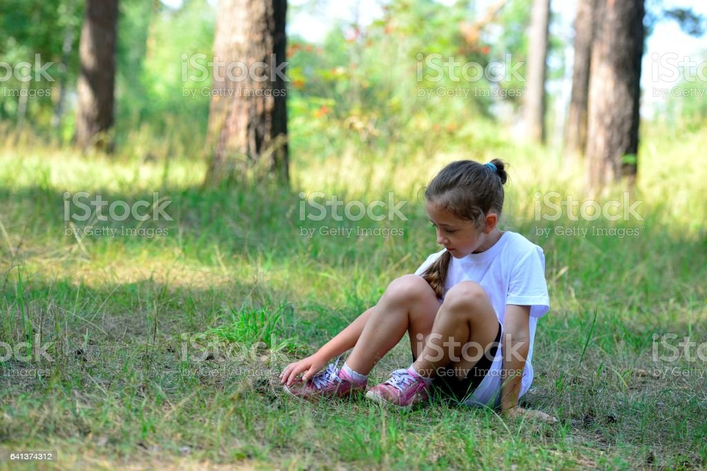 The girl has a rest after a short jog in the woods стоковое фото