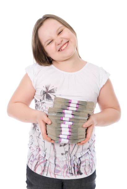 das mädchen hält einen stapel von geld - kindergeldantrag stock-fotos und bilder