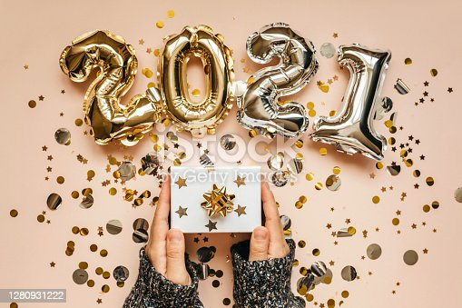 The girl holds a box with a gift in her hands. Nearby confetti and gold and silver numbers 2021. Festive New Year and Christmas concept background.