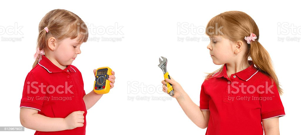 The girl holds in hand a digital multimeter and wrench stock photo