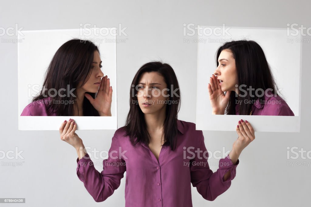 The girl holds in her hands two portraits, on which she gives herself a clue. stock photo