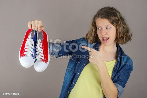 The girl holds sneakers in her hand, with the second hand her index finger points to sneakers.